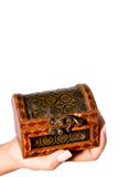 Wealth in your hand. Hand holding a small treasure chest Royalty Free Stock Image