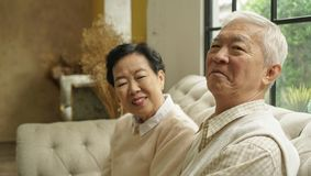Wealthy Asian elderly couple happy in luxury house. Smile at camera royalty free stock photography