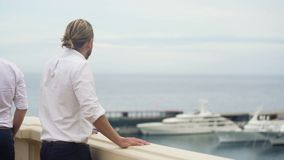 Wealthy billionaire looking at expensive yacht, luxury lifestyle of rich man. Stock footage stock footage