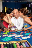 Wealthy blackjack player flirting with two women Stock Images
