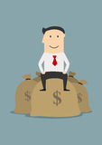 Wealthy businessman sitting on money bags Stock Photography