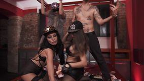 Wealthy hip hop men topless with girls standing on bed rapping. Wealthy caucasian hip hop men topless clothes glasses and snapbacks with girls in underwear stock video
