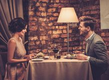 Wealthy couple enjoying meal at restaurant. Royalty Free Stock Photography
