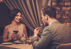 Wealthy couple enjoying meal at restaurant. Stock Photos