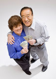 Wealthy couple excitedly holding group of twentys Royalty Free Stock Image