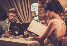 Wealthy couple with menu in a restaurant. Stock Photos