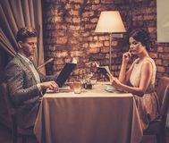 Wealthy couple with menu in a restaurant. Stock Images