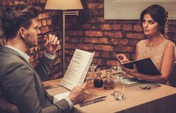 Wealthy couple with menu in a restaurant. Stock Photography
