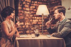Wealthy couple toasting with champagne in a restaurant. Stylish wealthy couple toasting with champagne in a restaurant Royalty Free Stock Photo