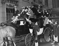 Wealthy group of people in horse drawn carriage Stock Photos