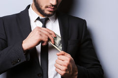 Wealthy handsome. Close-up of young man in formalwear putting money in his pocket while standing against grey background Stock Photos