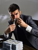 Wealthy hipster. Bearded man count dollars while smoking cigar. Successful businessman hold cash money. Rich man with. Beard in formal wear. Business and royalty free stock photography
