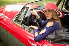 Wealthy lady looking out her classic red european sports car Stock Image