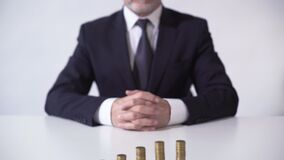 Wealthy man sitting in front of coin piles, growth of deposit interest, banking. Stock footage stock footage