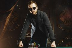 Money gambling for men. A wealthy mature man drinking whiskey and playing poker with the excitement in a casino. Gambling, playing cards and roulette royalty free stock image