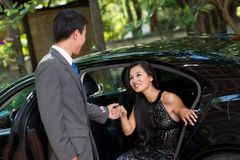 Wealthy relationship. Elegant men helping his wealthy lady to come out of the car Stock Photos