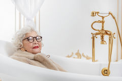 Wealthy senior lady relaxing in bathroom Stock Images