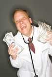 Wealthy successful dctor. A metaphorical image of a wealthy successful doctor showing US dollar banknotes he earned Stock Image