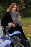 Wealthy woman in fur coat leaning on a sports car stock photography