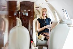 Wealthy Woman Holding Tablet Computer In Private. Portrait of wealthy mid adult woman holding tablet computer in private jet Stock Photography