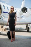 Wealthy Woman With Luggage Walking Against Private. Full length portrait of wealthy woman with luggage walking against private jet at airport terminal Stock Photo