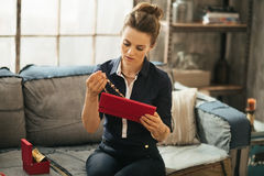 Wealthy woman sitting on couch in loft and unpacking jewelry box Royalty Free Stock Photos