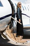 Wealthy Woman Stepping Out Of Private Plane. Full length of wealthy woman in elegant dress stepping out of private plane Stock Photos