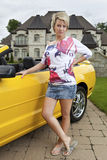 Wealthy young woman standing beside car Royalty Free Stock Photos