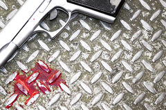 Weapon and Blood. Illustrative styled image of blood splatters and a hand gun on a steel drain cover. room for copy etc Stock Photography