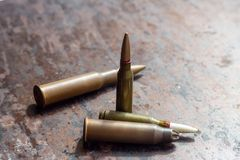 Weapon bullets on rusty metal background. Military industry, war, global arms trade and crime concept stock image
