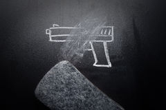 Weapon draw erased on blackboard - no violence concept. Idea Stock Photos