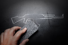 Weapon draw erased on blackboard - no violence concept. Idea stock images