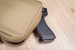 Weapon gun in bag, khaki or sand color, on table background Royalty Free Stock Image