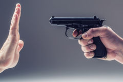 Weapon  gun. Men's hand holding a gun. The second hand is defending Royalty Free Stock Image