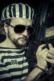 Weapon, Prison riot concept. Man holding a machine gun, prisoner Royalty Free Stock Photo