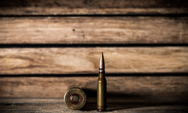 Weapons, cartridge on wooden background. Different weapons and the ammunition on wooden background, place for text Stock Photos
