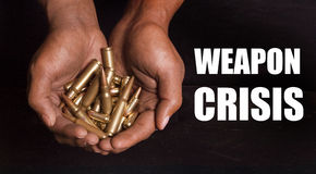 Weapons Crisis. Hands holding pistol and rifle ammunitions Royalty Free Stock Images