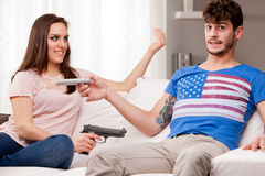Weapons: woman demanding for remote control Royalty Free Stock Image