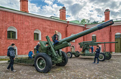 The weapons of the World War II at the walls of the fortress and the children playing around them. Royalty Free Stock Photo