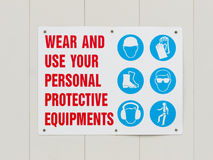 Wear personal protective equipments signboard. Signboard on hoarding outside construction site reminding workers to wear and use personal protective equipments Royalty Free Stock Photos