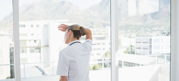 Wear view of confident female doctor looking through windows Stock Photo