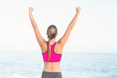 Wear view of fit woman looking at the sea with arms rise Royalty Free Stock Photo