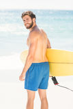 Wear view of handsome man holding surfboard Royalty Free Stock Photography