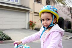 Always wear your helmet !. 3 yr old girle wearing a helmet on the street stock image
