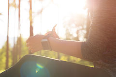 Wearable technology. Female athlete putting on her her smart watch to monitor workout performance. Lifestyle wearable technology shot with lensflare. Female Royalty Free Stock Photography