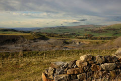 Weardale quarry view. View looking west over Weardale with abandent quarry and old stone walling. Heavy darkking clouds moving in Royalty Free Stock Photo
