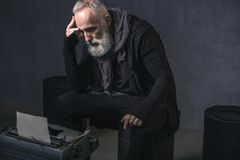 Wearied retire writer situating near printing machine. Where is my muse. Side view tired bearded senior author dreaming while locating on iron cask in room Royalty Free Stock Image