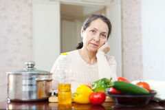 Weariness mature woman at  kitchen. Weariness mature woman with  vegetables at her kitchen Stock Photo