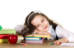 Weariness  schoolgirl. With long curl in black and white uniform sitting at the table with  many colorful books, pencils, red beautiful apple  and laying head Stock Image