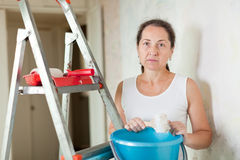 Weariness  woman makes repairs at home. Weariness mature woman makes repairs at home Royalty Free Stock Photos